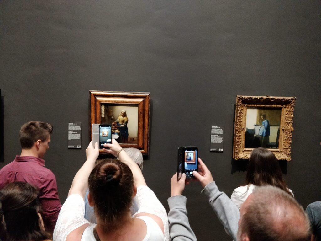 Menschen im Rijksmuseum machen Fotos von den Gemälden mit ihren Smartphones